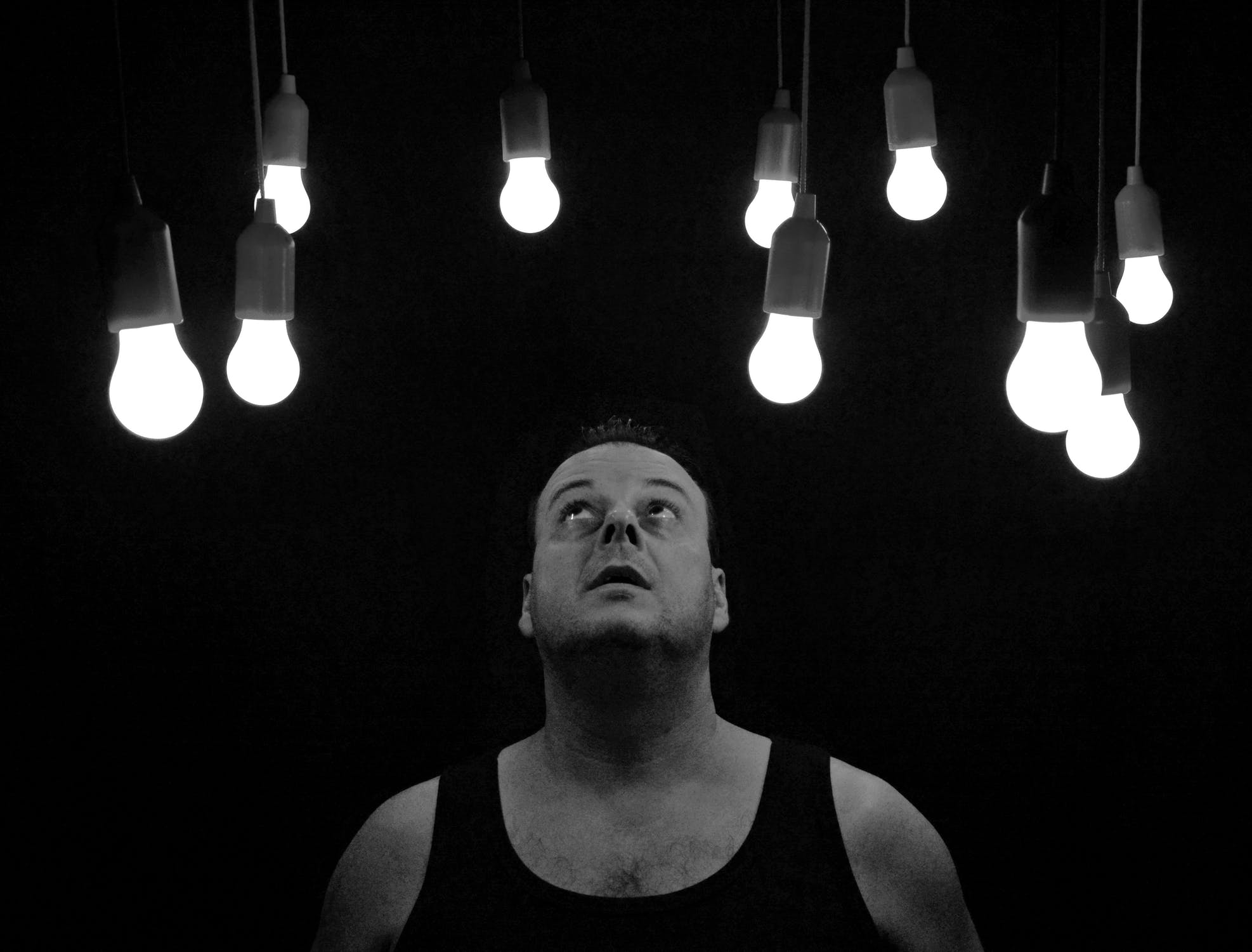 man looks at light bulbs